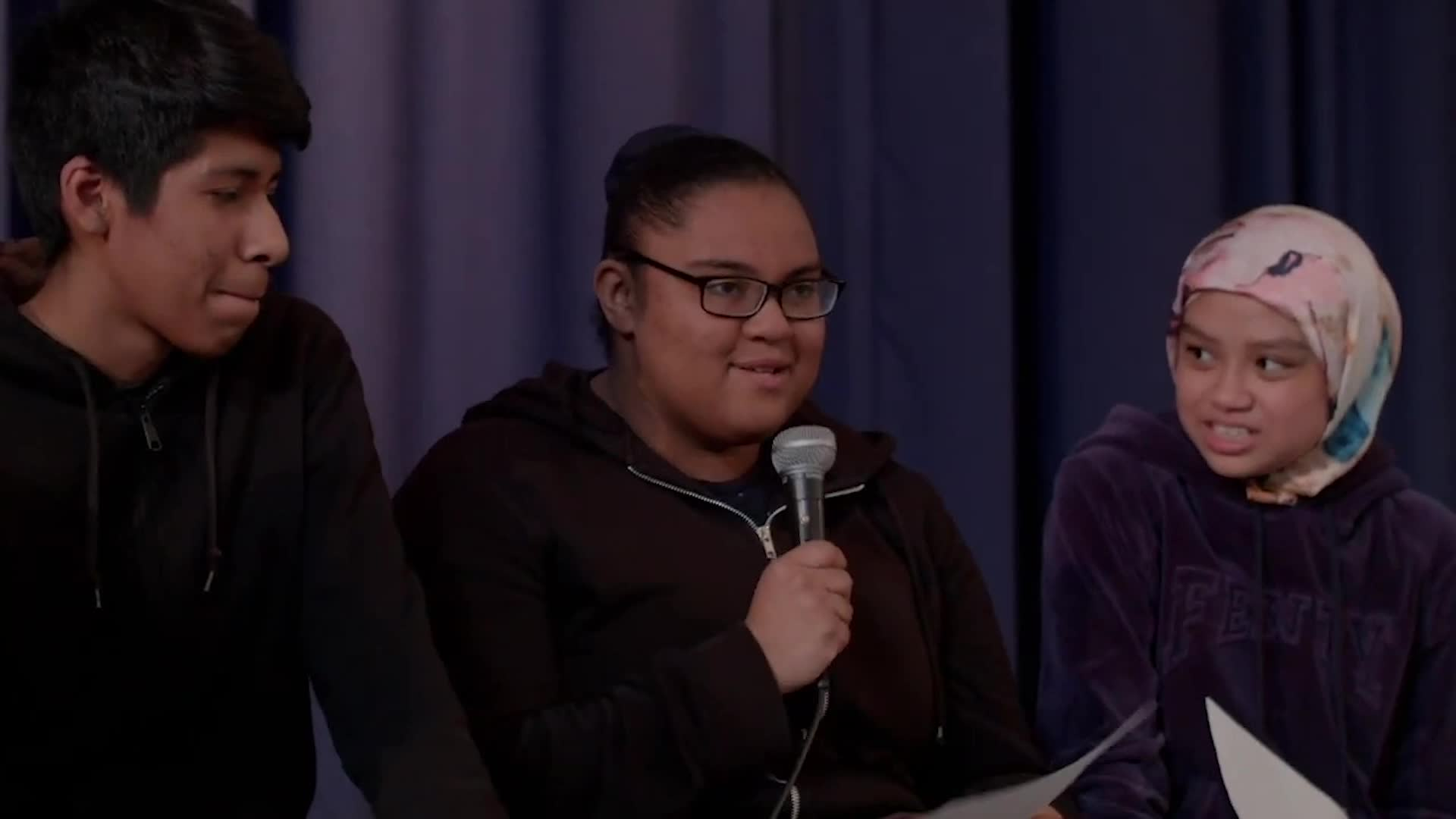 Several students sit on the edge of a stage. One by one they pass and speak into a microphone. At the end of the video, there are closeups of various collages made from text cutouts.