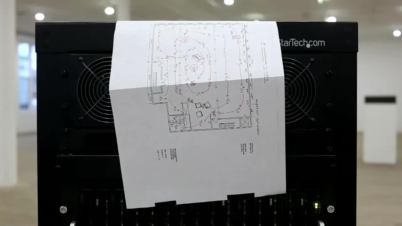 A video of a paper diagram blowing from the wind of a computer device. The top right corner of the machine reads,
