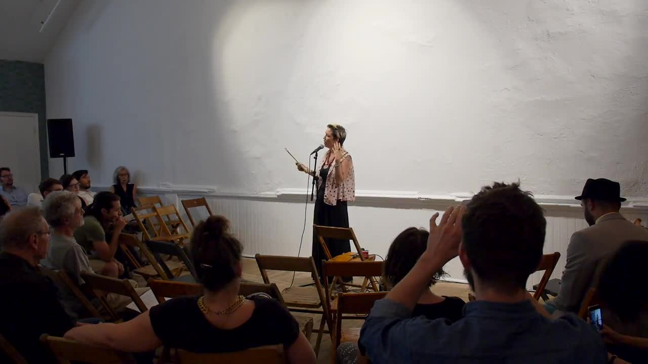 Video documentation of a woman performing a reading for a seated audience.