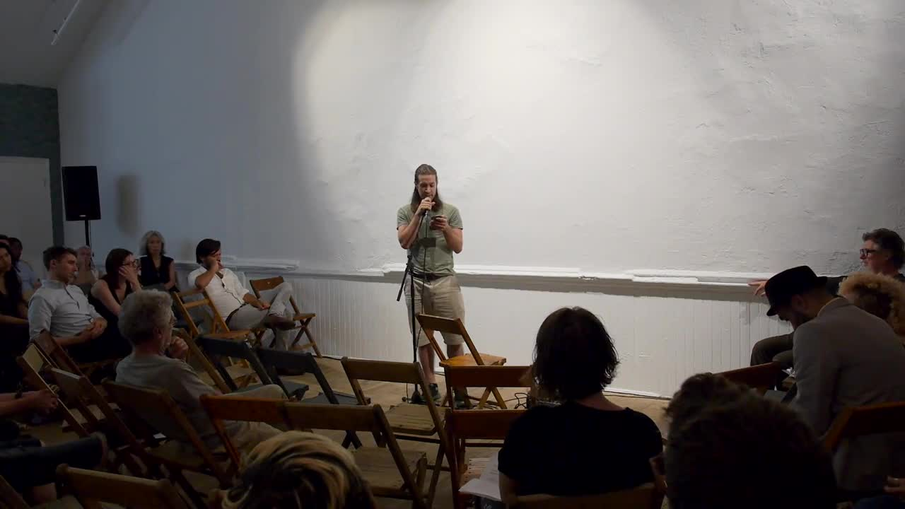 Video documentation of a man performing a reading for a seated audience.