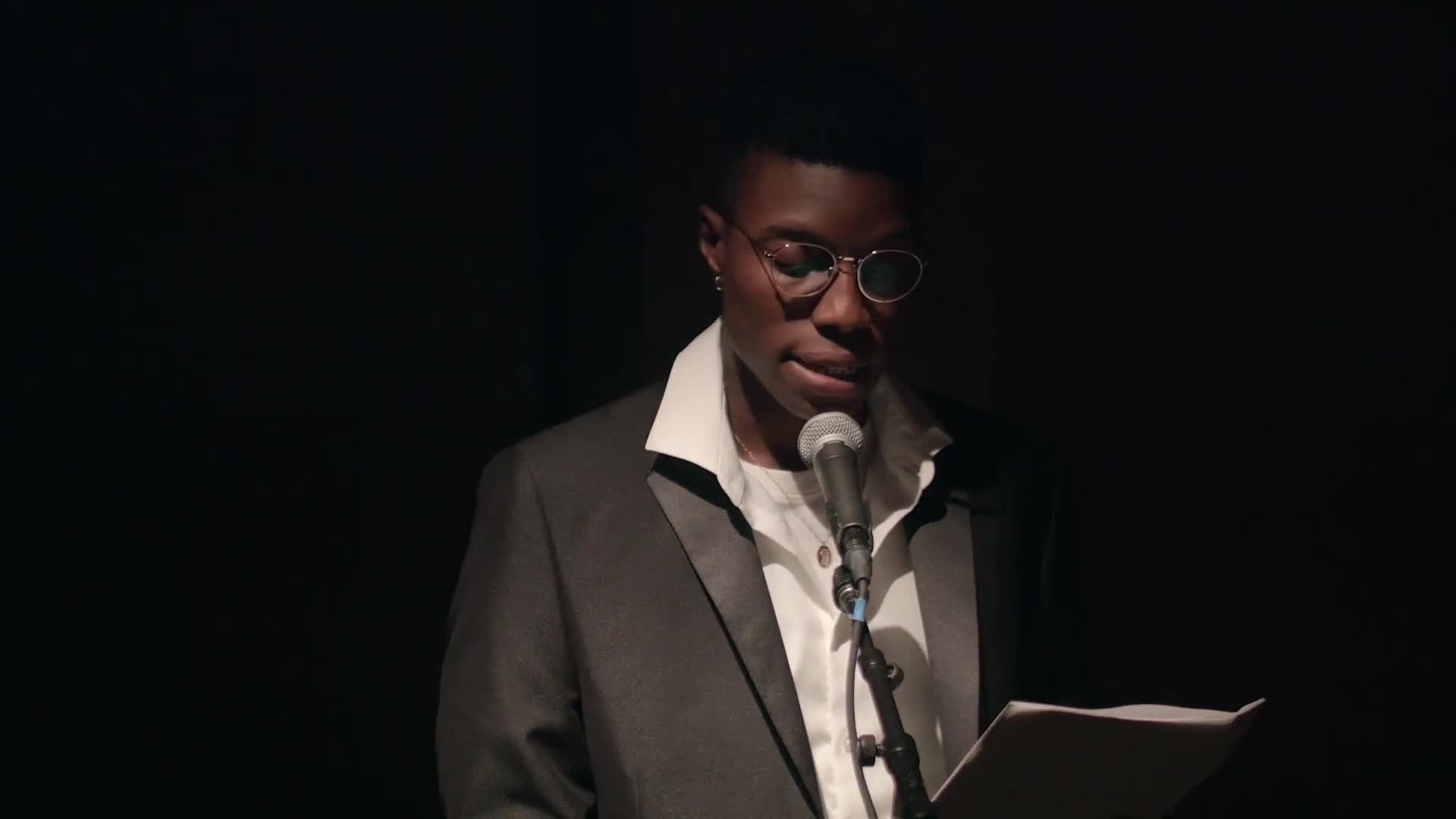 Aria Dean enters the spotlit center of a dark room, sets down a glass of water, and adjusts the microphone to the correct height.  She is wearing a black suit with a white shirt and reads off of a piece of paper in her right hand to a seated audience.