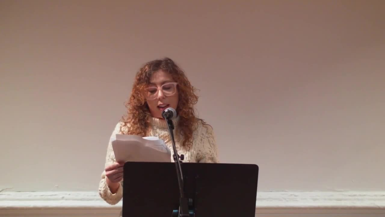 A figure wearing glasses and a white sweater reads from a text, speaking into a microphone.