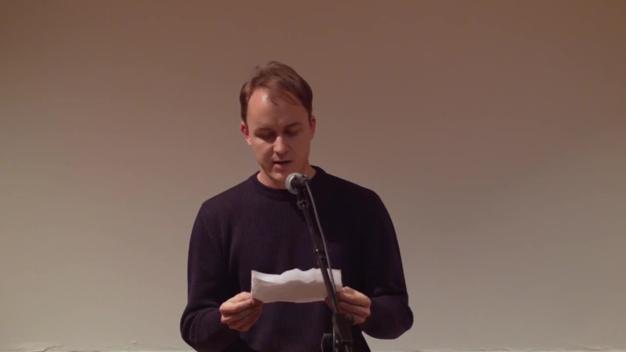 A figure reads a printed letter to an audience, speaking into a microphone.