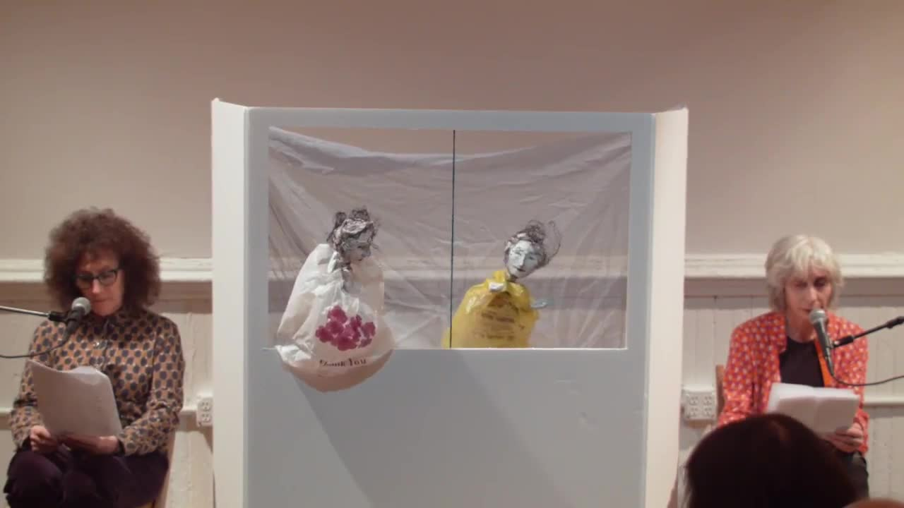Two people sit on either side of a small puppet theater, reading from a printed text. Two puppets dressed in plastic bags perform as they read.
