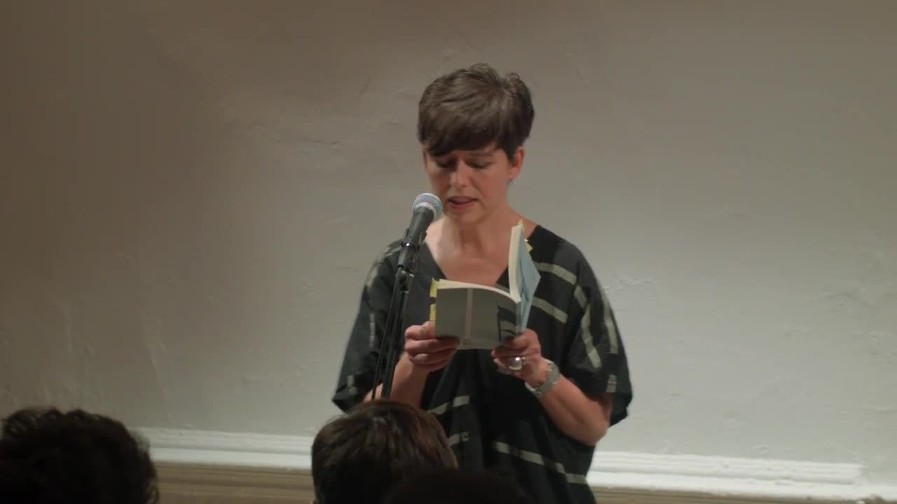 Video documentation of a woman reading from a book in front of a microphone.