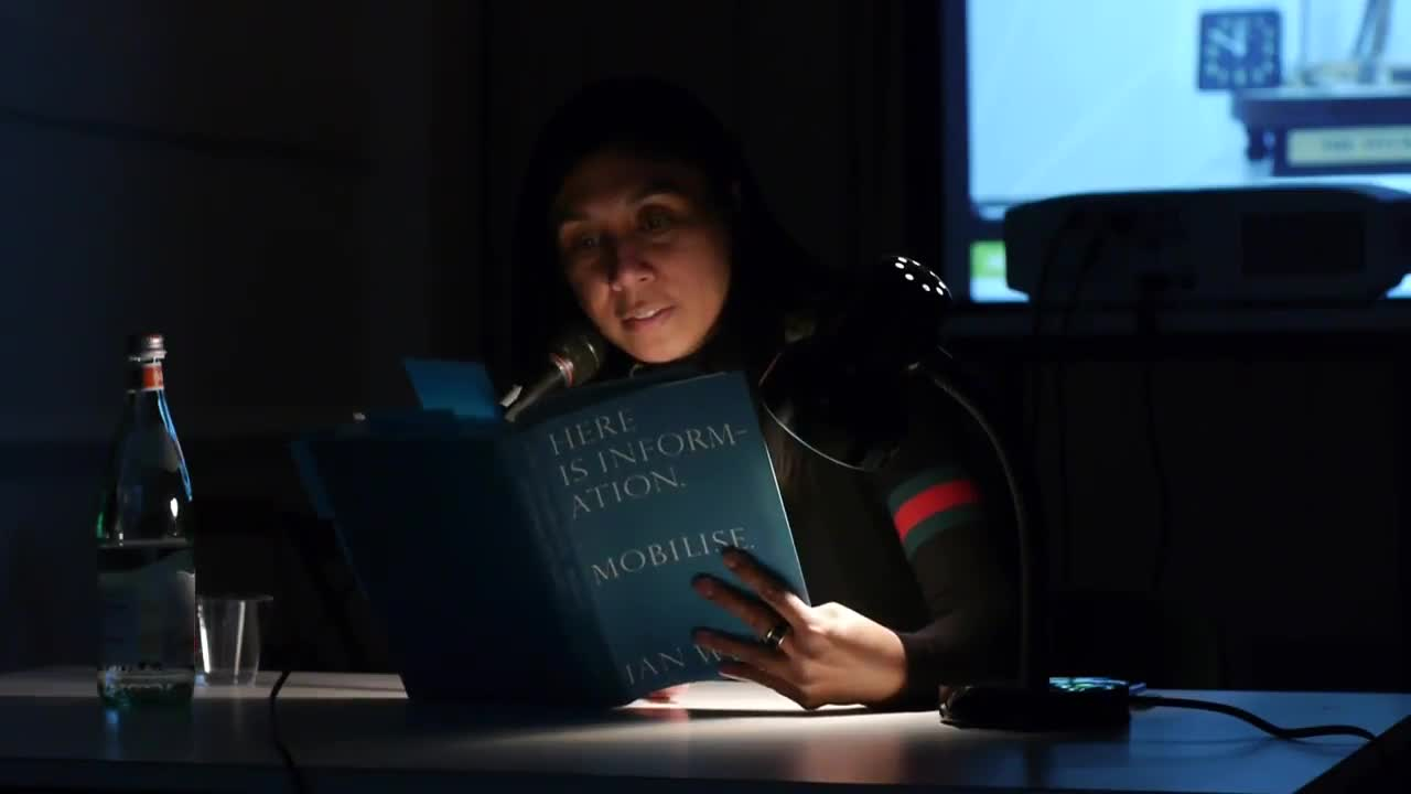A person reads from a book illuminated by a lamp on a table in a dark room.