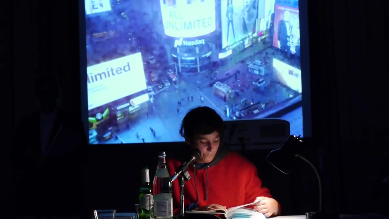 A person reads from a book illuminated by a lamp on a table in a dark room, with a video depicting an aerial view of Times Square projected in the background.