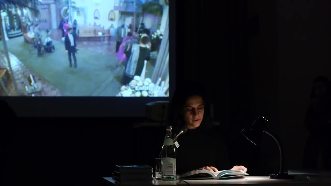 A person reads from a book illuminated by a lamp on a table in a dark room, with a video of a wedding in the background.