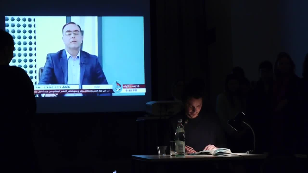 A person reads from a book illuminated by a lamp on a table in a dark room, with a video of an Arabic news channel projected in the background.