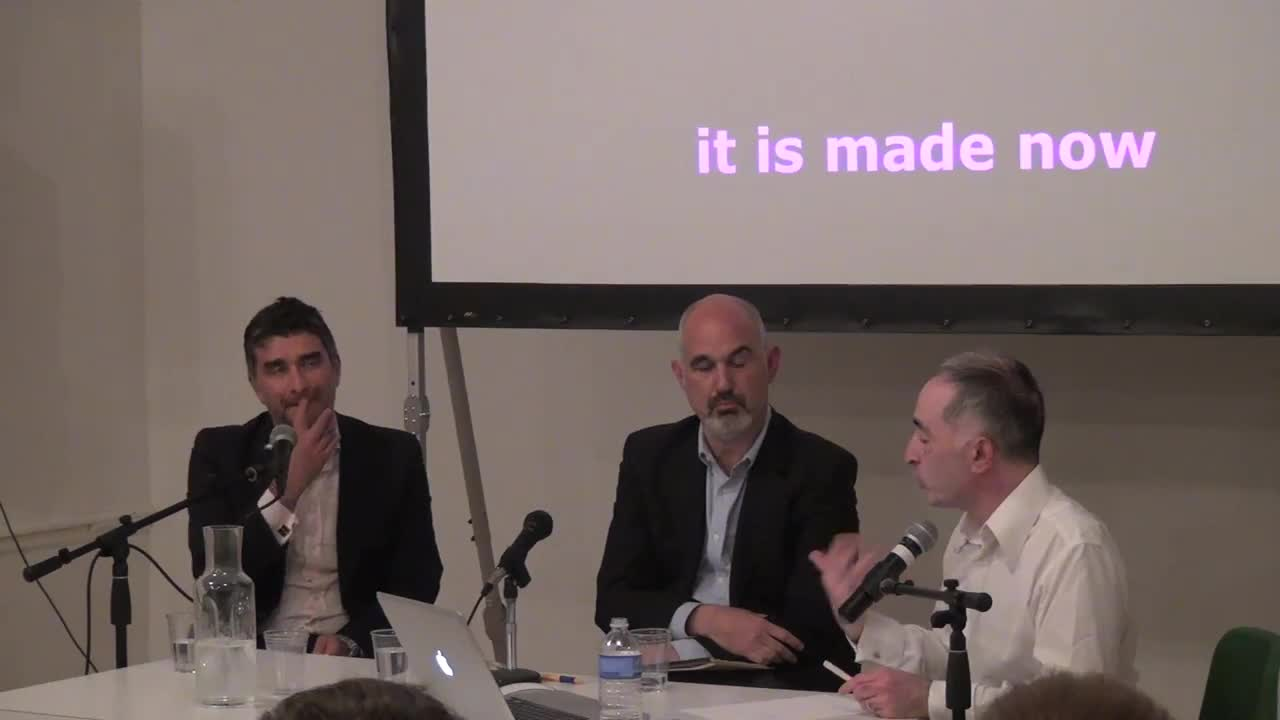Three seated men speak in turn in front of a projected screen with key phrases.