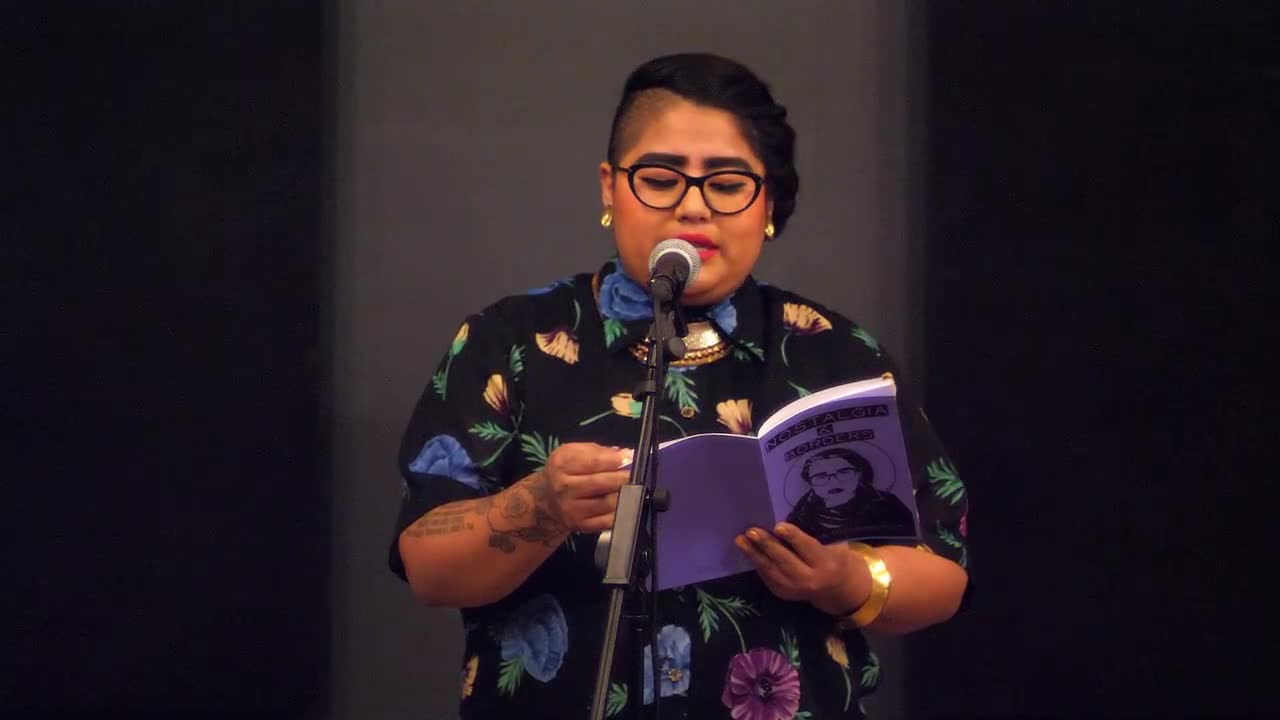 A person reads from a small purple book titled