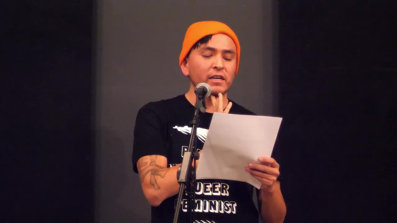 A person reads from a printed text on a microphone