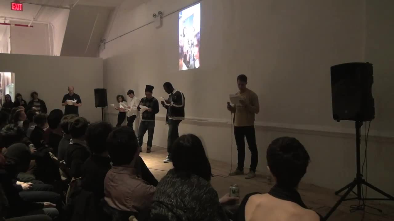 Video documentation of a group of people performing with script in hand.
