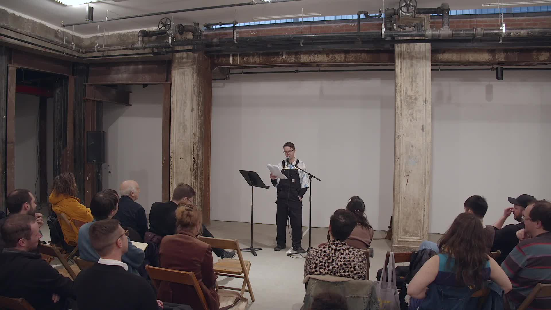 Ted Rees is shown standing against a white wall in a large room with metal columns, facing the camera and an audience seated in wooden folding chairs.  He reads from a stack of papers in his right hand and speaks into a microphone.  The camera occasionally zooms in to show him from the waist up, then returns to filming the whole room.