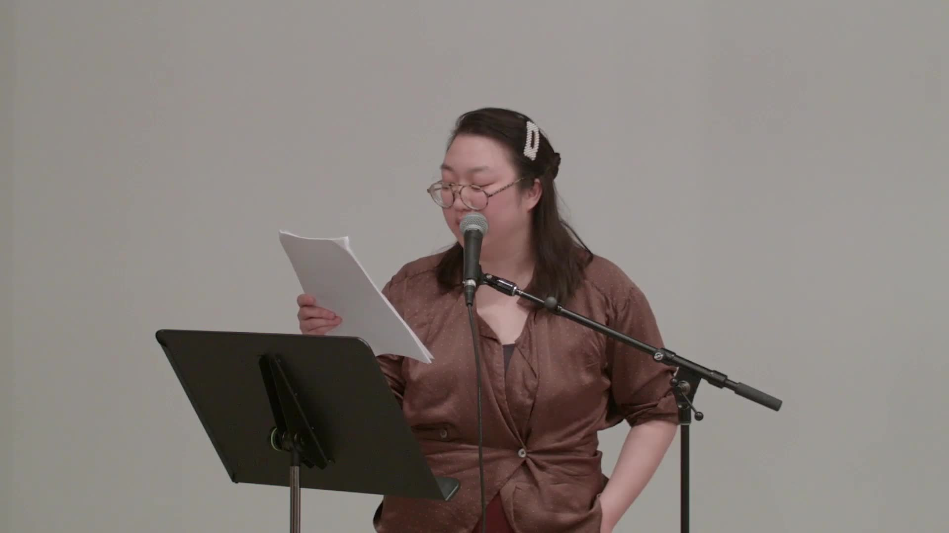Oki Sogumi is shown standing against a white wall in a large room with metal columns, facing the camera and an audience seated in wooden folding chairs.  She reads from sheets of paper in her hand and speaks into a microphone.  The camera occasionally zooms in to show her from the waist up, then returns to filming the whole room.
