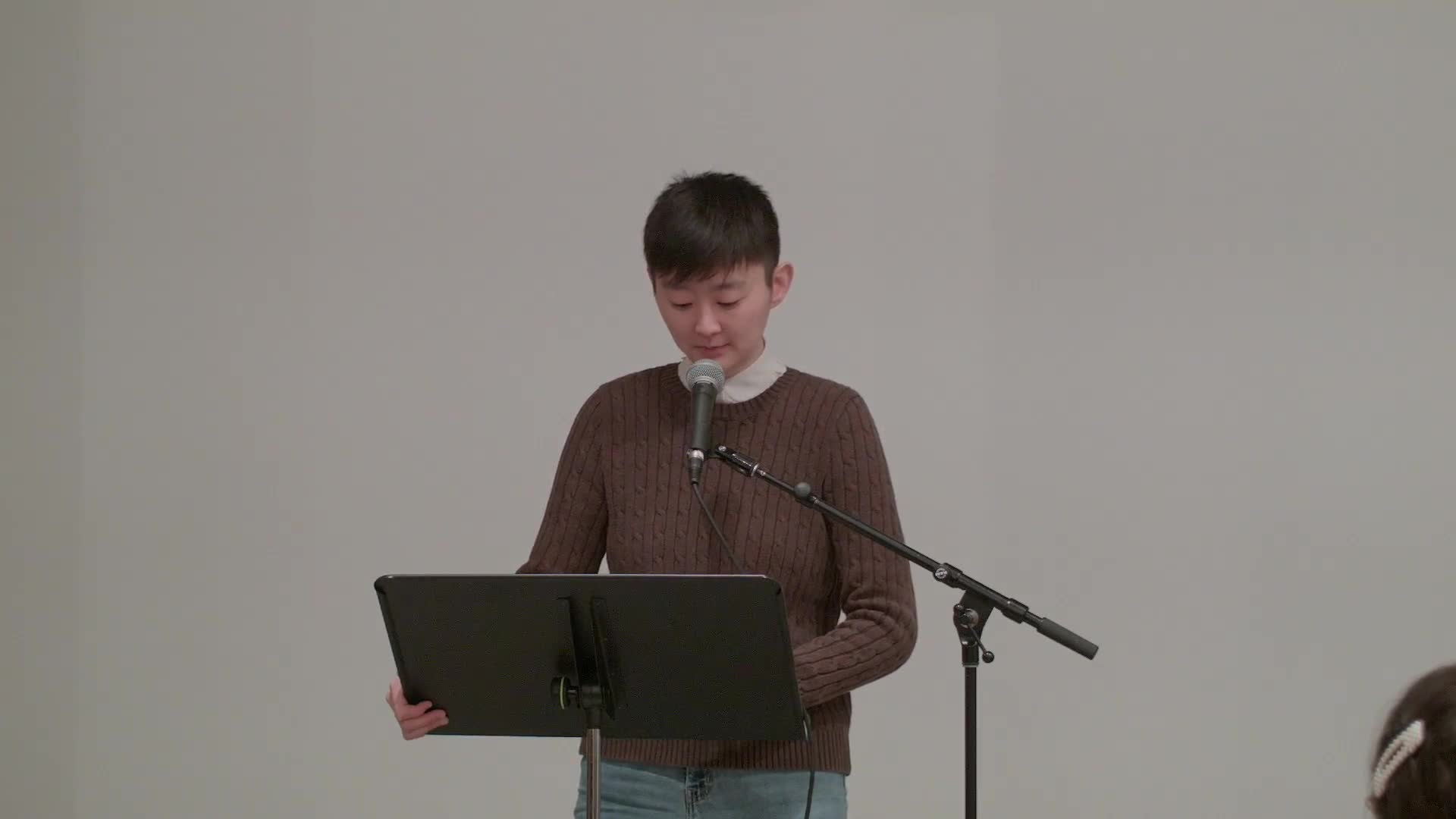 Joo Hyun Kim is shown standing against a white wall in a large room with metal columns, facing the camera and an audience seated in wooden folding chairs.  They read their text from a music stand in front of them and speak into a microphone.  The camera occasionally zooms in to show them from the waist up, then returns to filming the whole room.