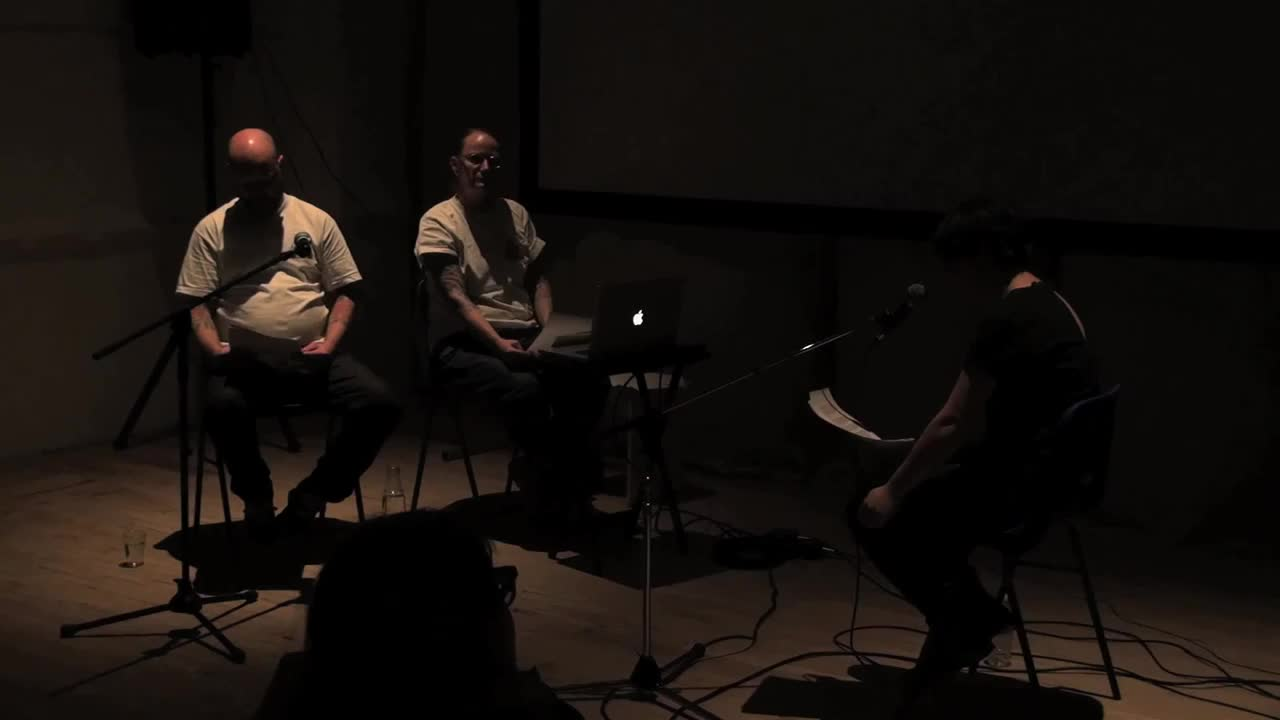 Three people speaking from a script in a dark room, intercut with various video montages.