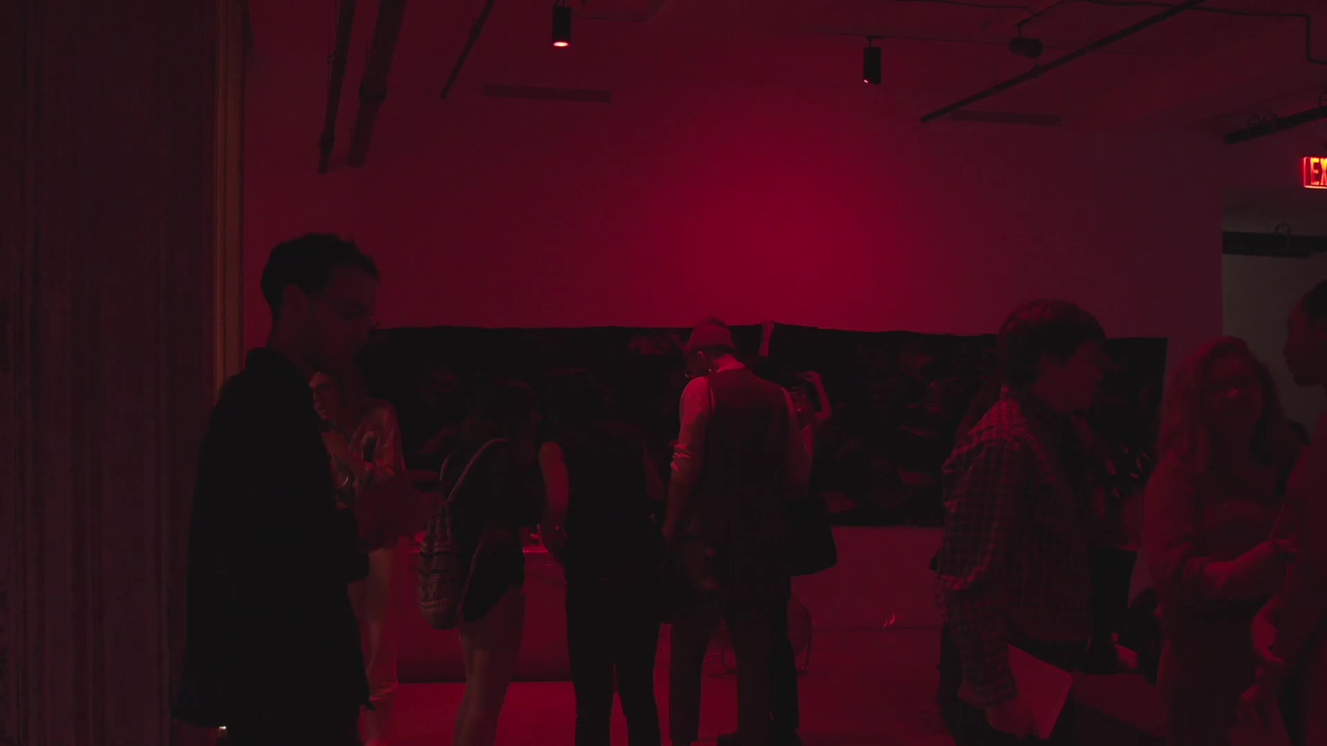 A person plays music and wanders around the room. Scenes of food, video projections with people dancing and crowds mingling are intercut throughout.