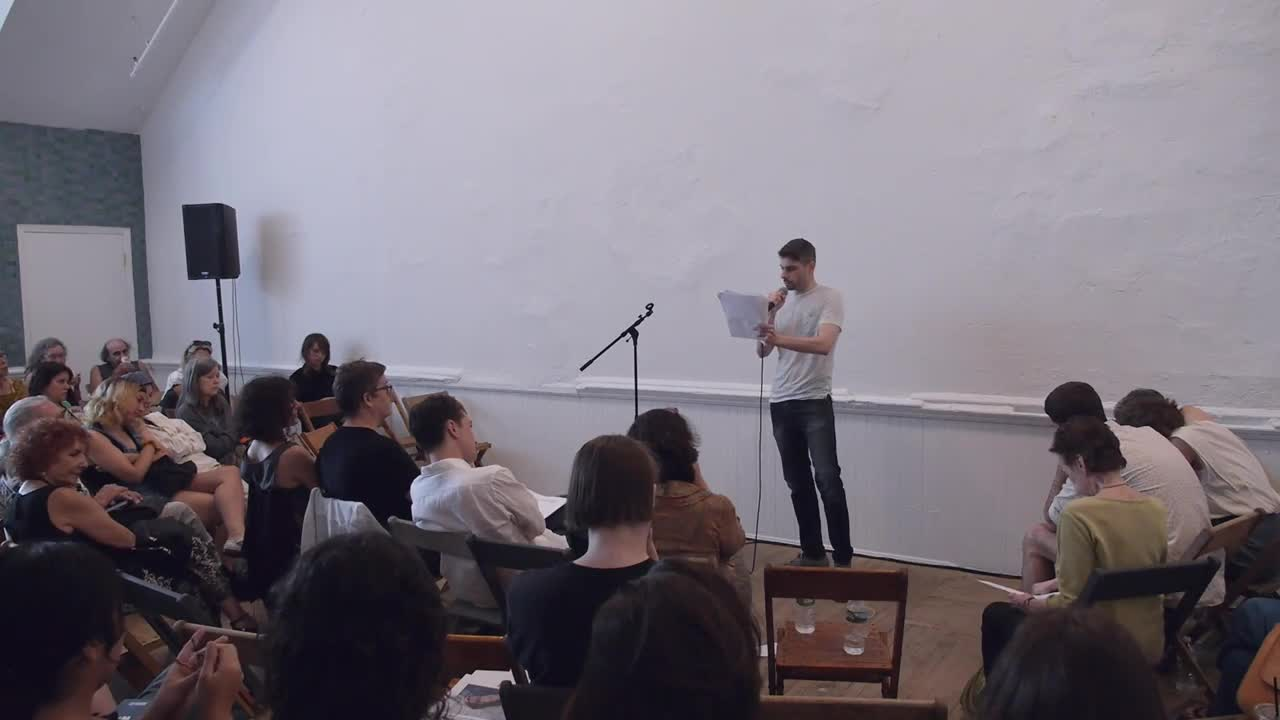 A person reads from printed paper in front of a seated audience.
