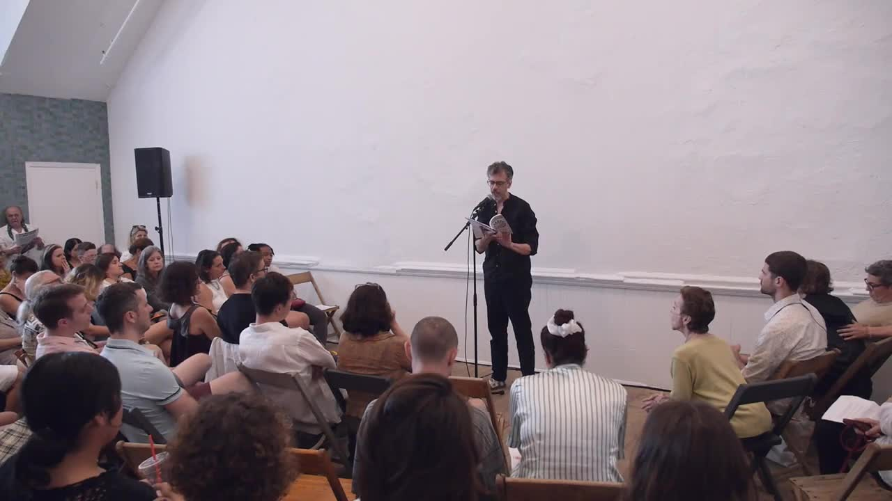A person reads from a sheet of paper and a book to a seated audience.