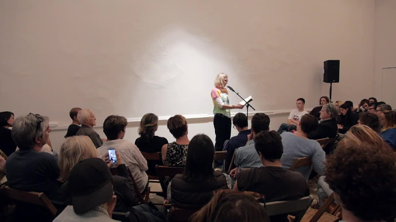 Two people read in front of a small crowd