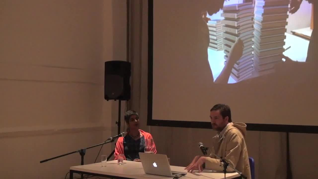 Video documentation of a man and woman seated at a table, giving a talk with a PowerPoint presentation projected on a screen behind them.