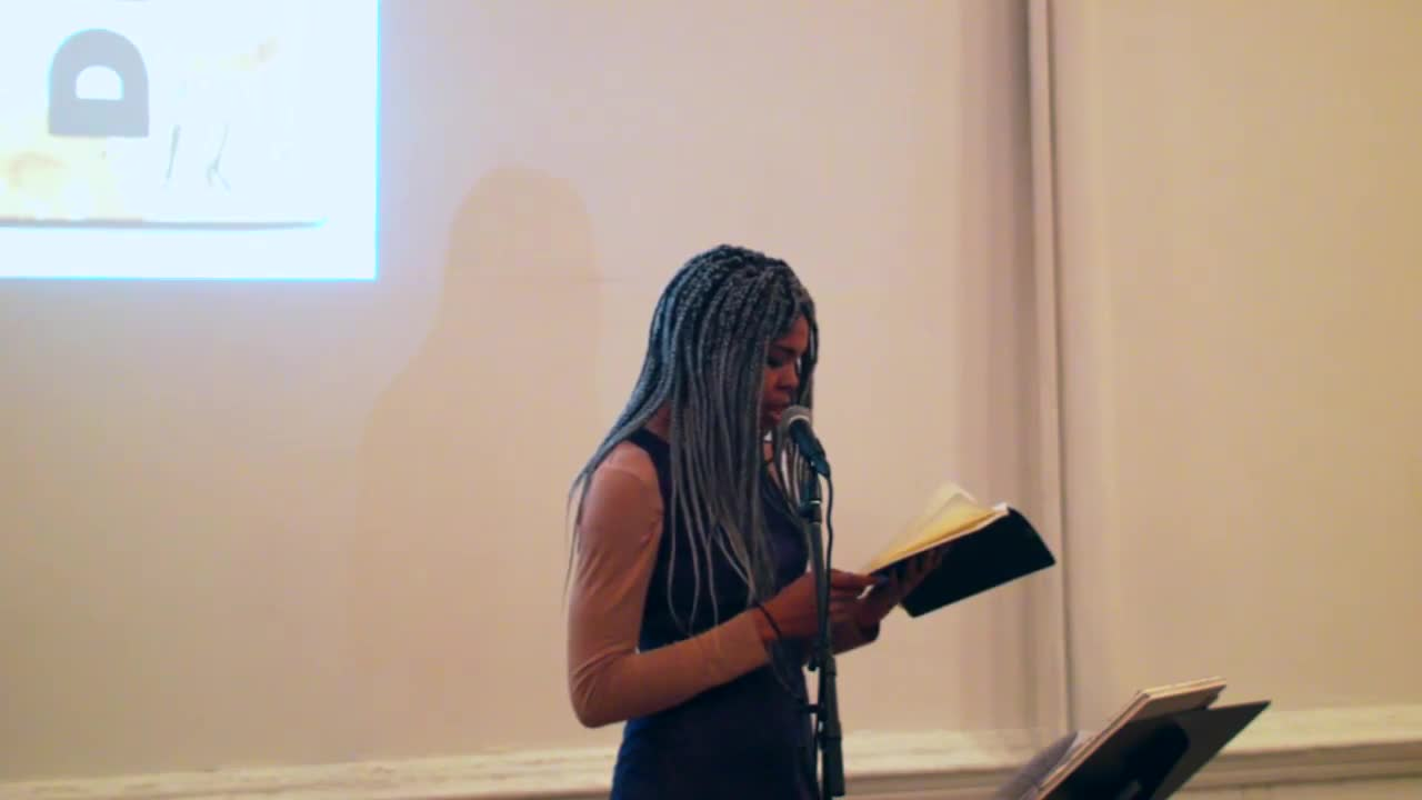 A person reads from several sheets of printed paper to an audience