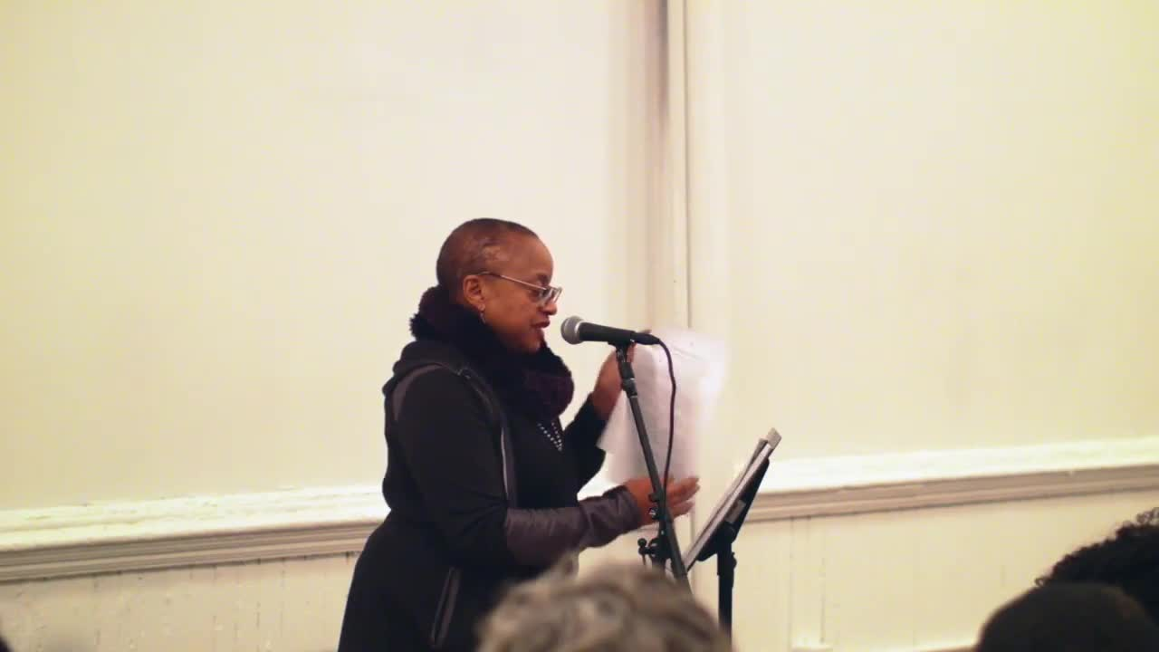 A person reads from papers on a music stand, speaking to an audience with a microphone.