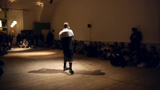 Video documentation of performers moving in the middle of a spotlit room, with the audience seated in a rectangle around them.