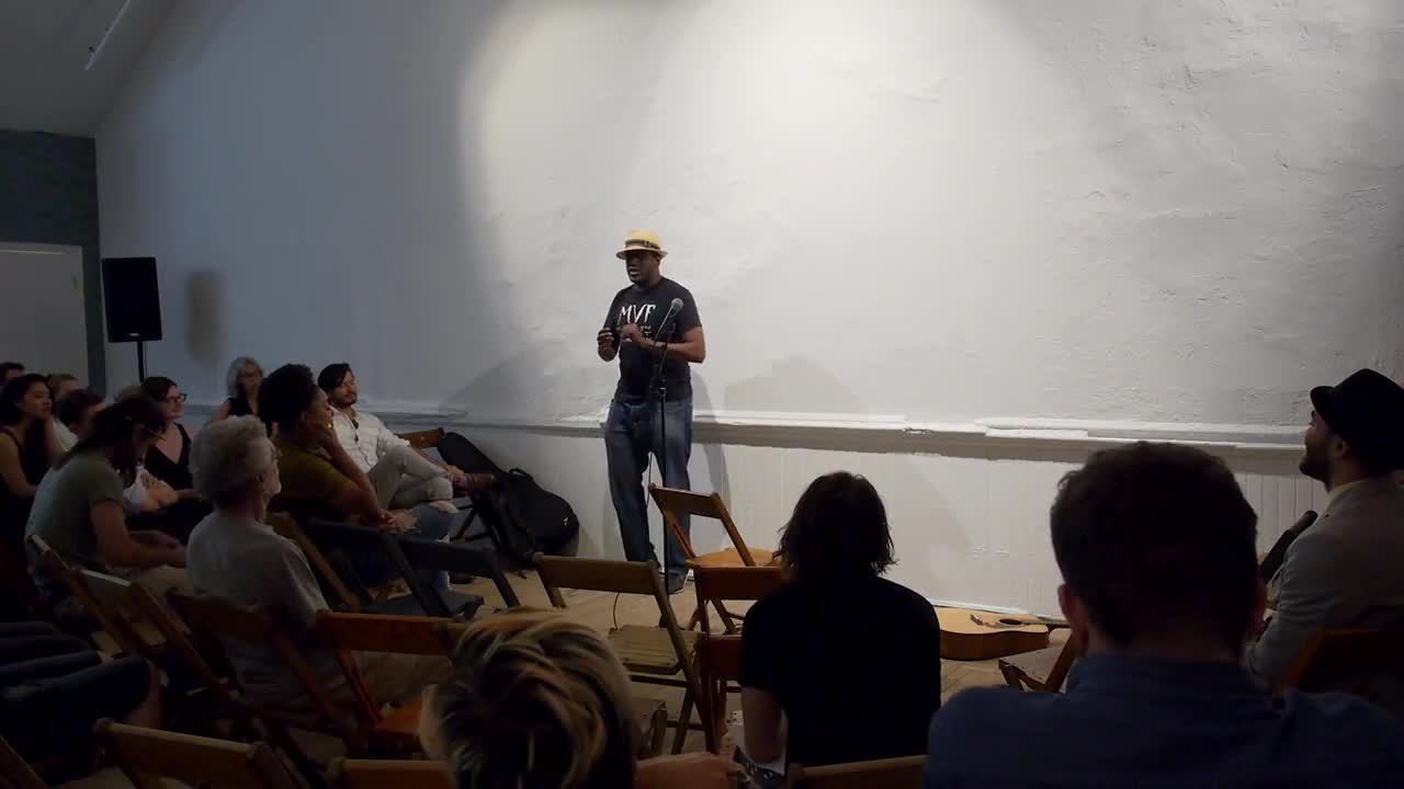 Video documentation of a man with a guitar performing a reading for a seated audience.