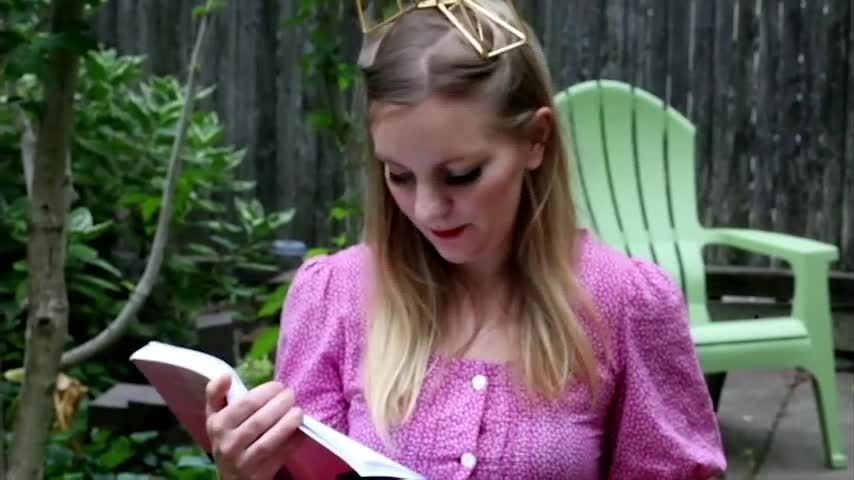 A video of a woman in a pink dress sitting at a table in a yard surrounded by stuffed animals and a tea set. A man prepares tea and follows her around the yard as she tries to avoid him, eventually forcing her to drink the tea. At the end, the cover of <em>Titanic</em> by Cecilia Corrigan is shown.