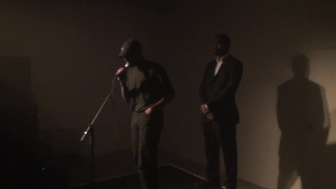 Video documentation of a performance by a man dressed in black clothing and a hat.
