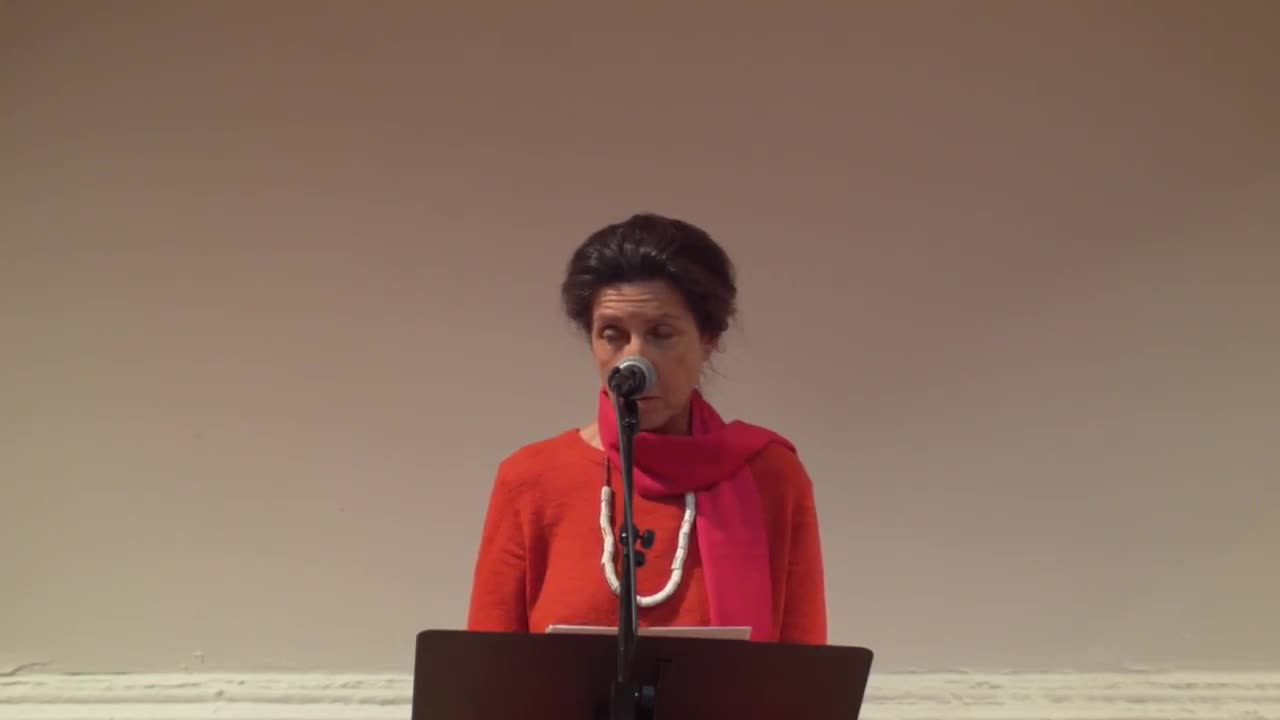 A figure in a red sweater reads from a text, speaking into a microphone.
