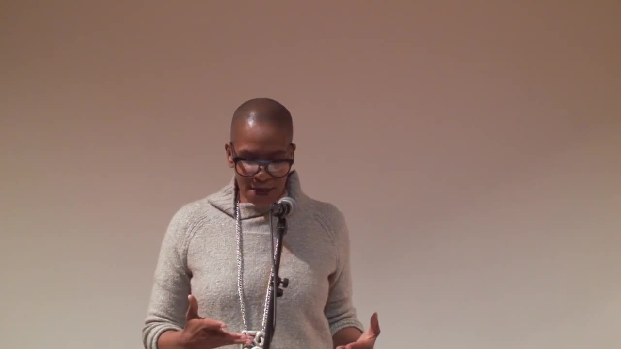 A figure wearing glasses speaks to an audience through a microphone.