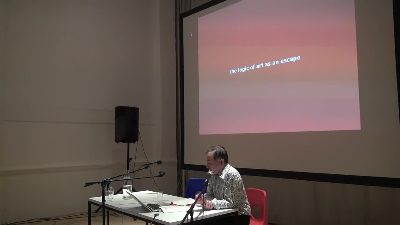 A seated man gives a talk with key phrases projected on a screen behind him.