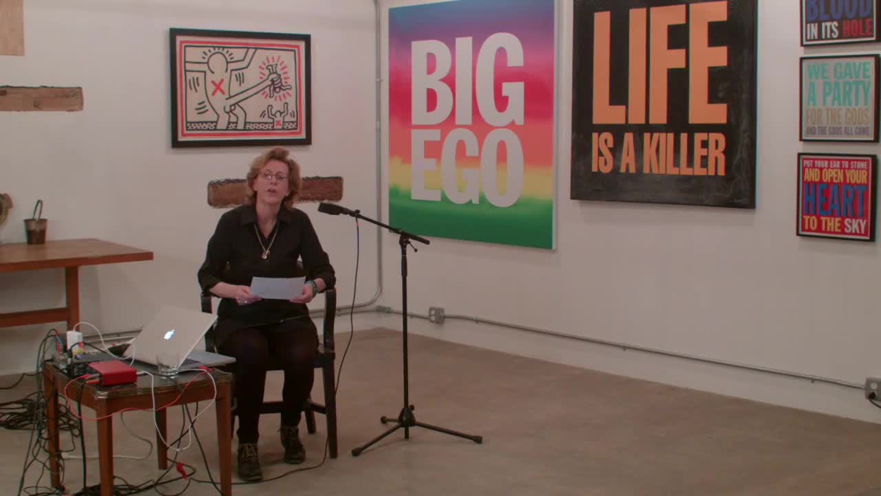 A woman sitting next to a laptop and audio interface in front of several Giorno posters, speaking into two microphones with a variety of props.