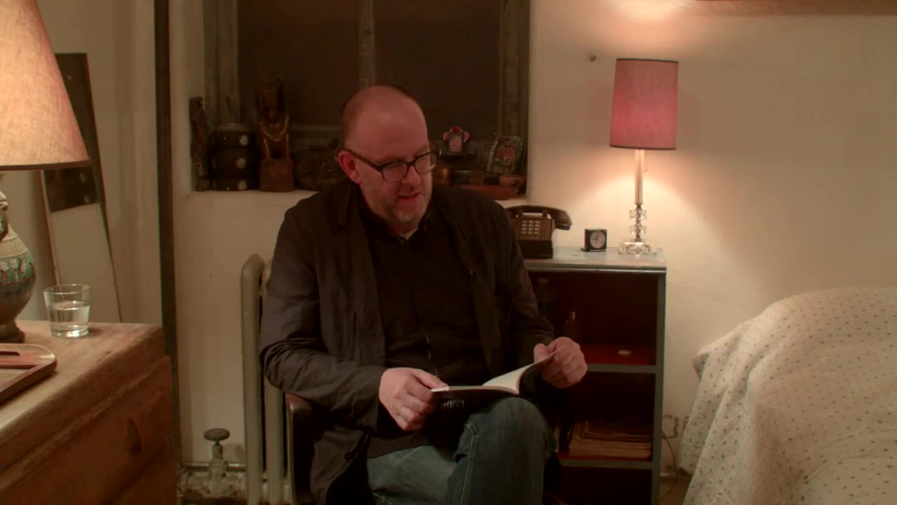 A man sits on a chair and reads from a small book in a bedroom.
