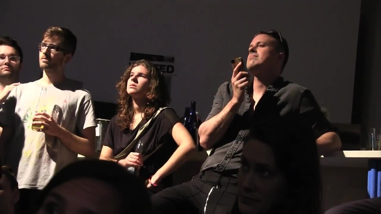 Two performeres surrounded by audience members in an intimate space.