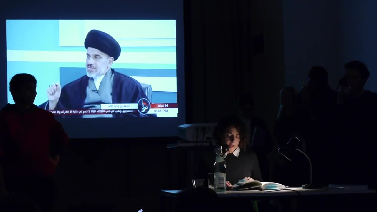 A person reads from a book illuminated by a lamp on a table in a dark room, with an Arabic news channel interview projected in the background.