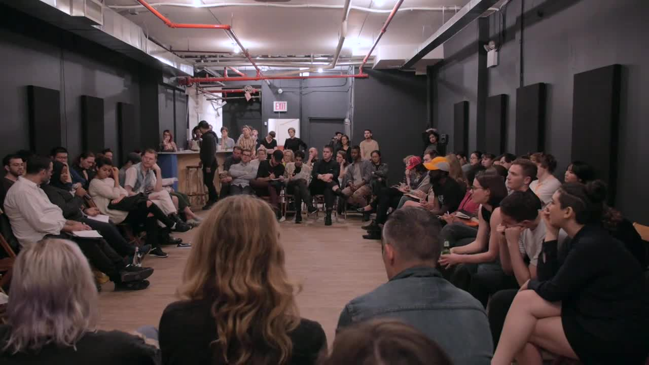 Several people speak on microphones among a crowd sitting in a circle around a room.