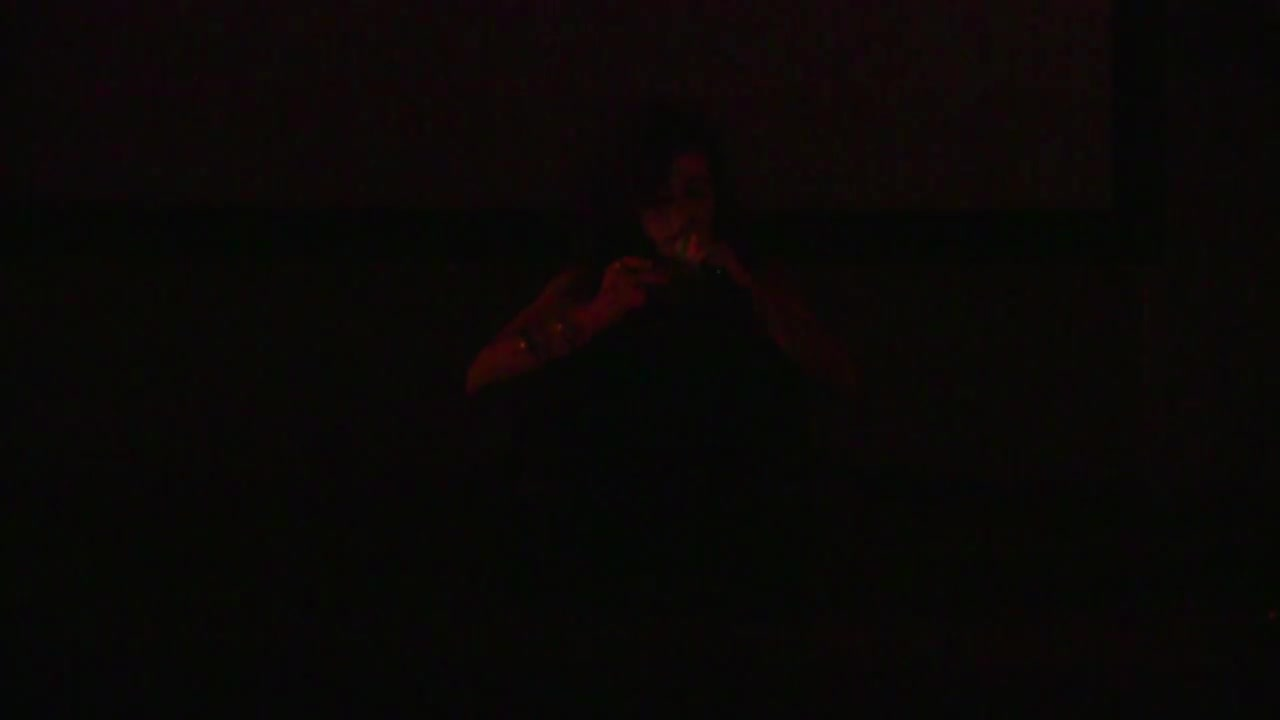 A figure illuminated by a red light in an otherwise dark space speaks into a microphone as they read a text.