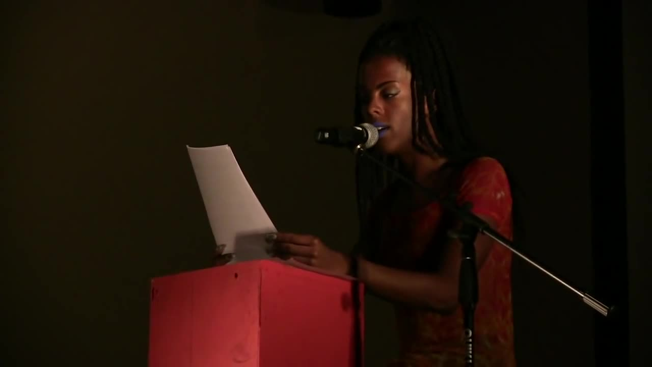 A figure sits behind a red podium and speaks into a microphone as they read from a piece of paper.