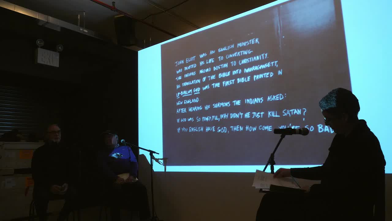 Video documentation of a discussion held in front of an accompanying slide presentation.