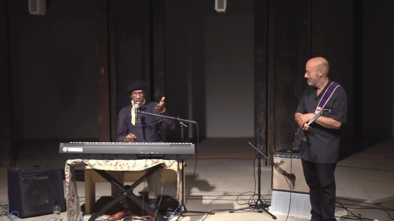 [Video documentation of multiple individuals speaking and playing music.]