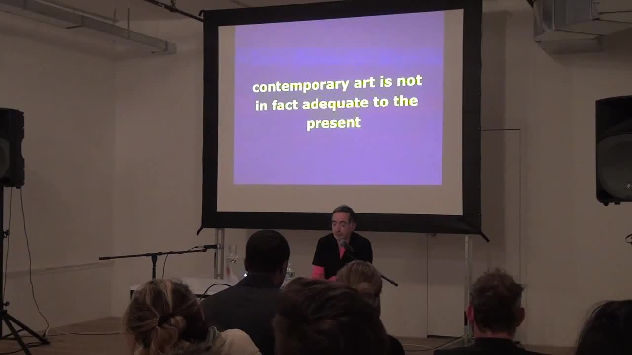 Video documentation of a man giving a talk with a PowerPoint presentation.