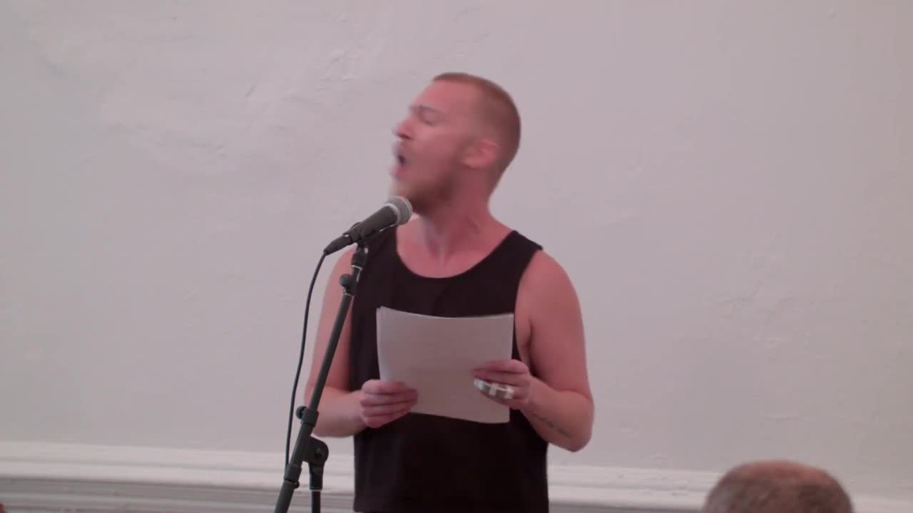A person reading from printed paper in front of a seated audience.