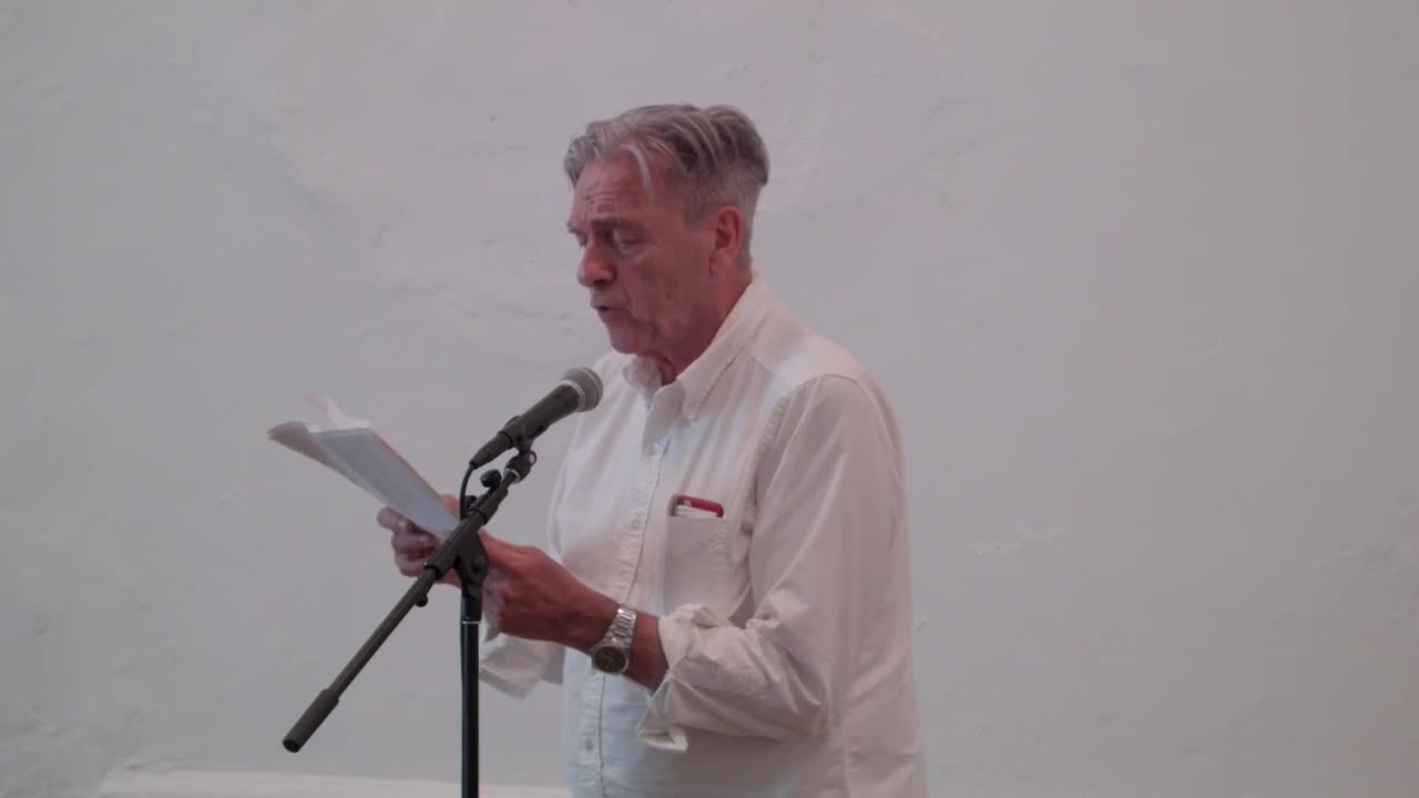 A person reading from a printed text in front of a small audience.