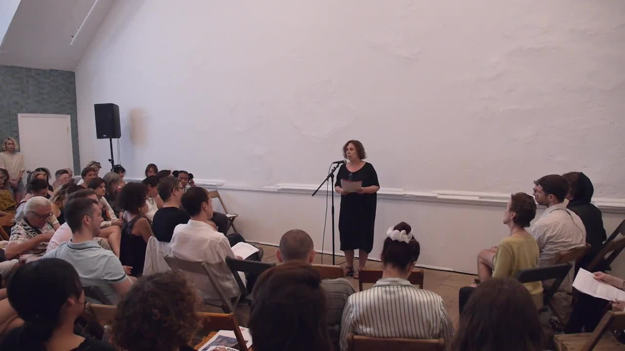 A person reads to a seated audience.