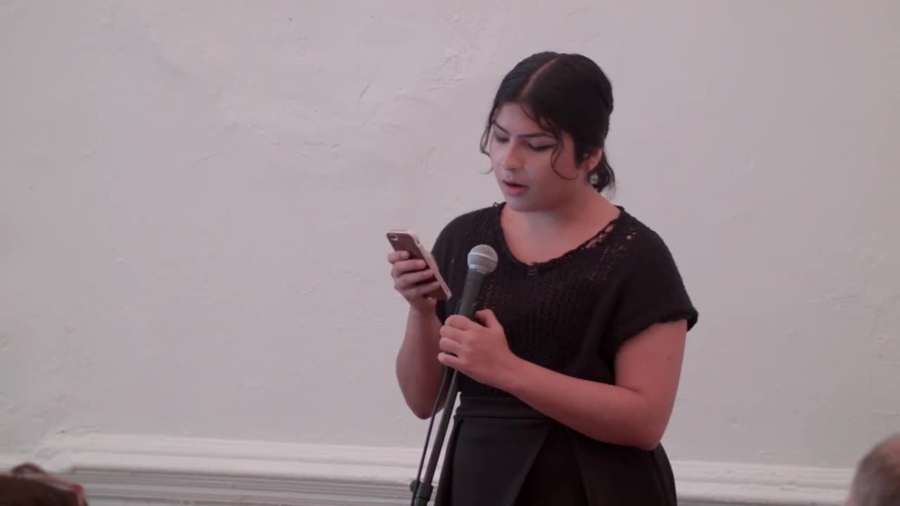 A person reading from a mobile phone in front of an audience.