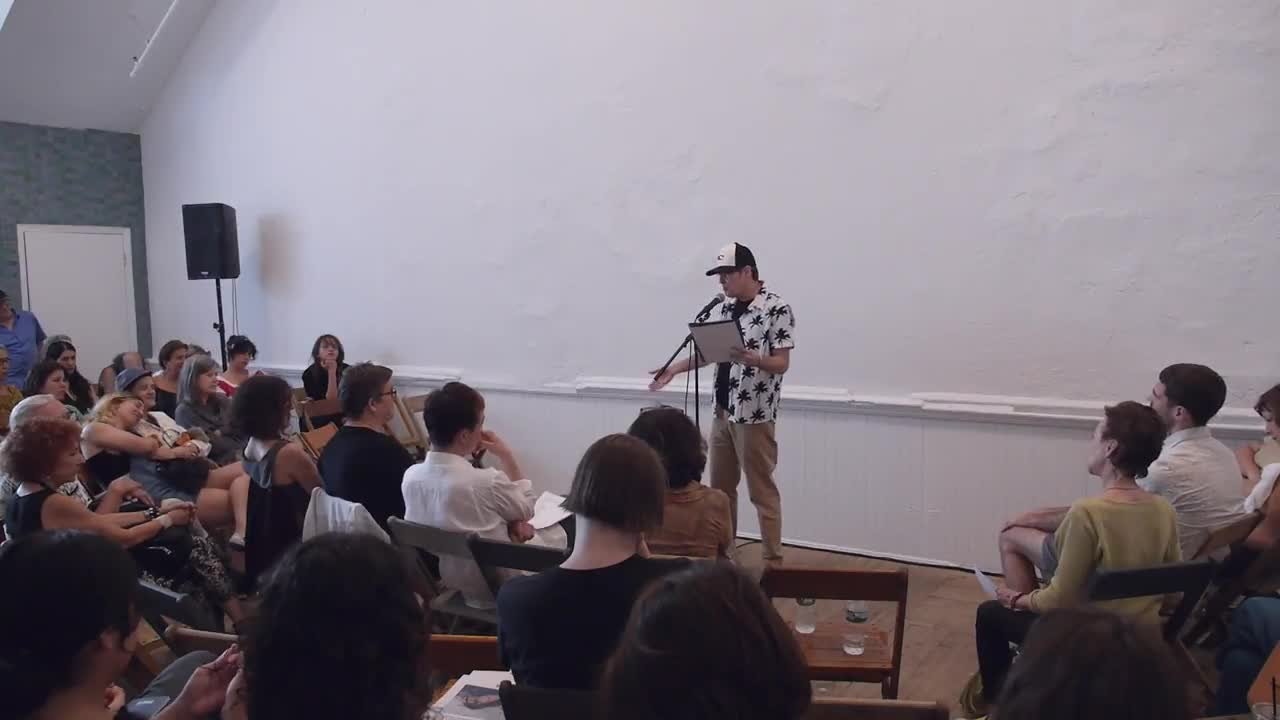 A person reads in front of a seated audience.